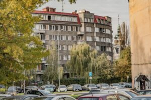 Kamienica przy ul. Bohaterów Warszawy i wieża ratusza w tle.