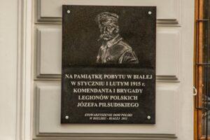 Tablica pamiątkowa na ścianie budynku poczty.
