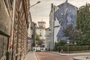 Ulica Mickiewicza z muralem ''Blue Monday'' i wieżą Zamku Sułkowskich.